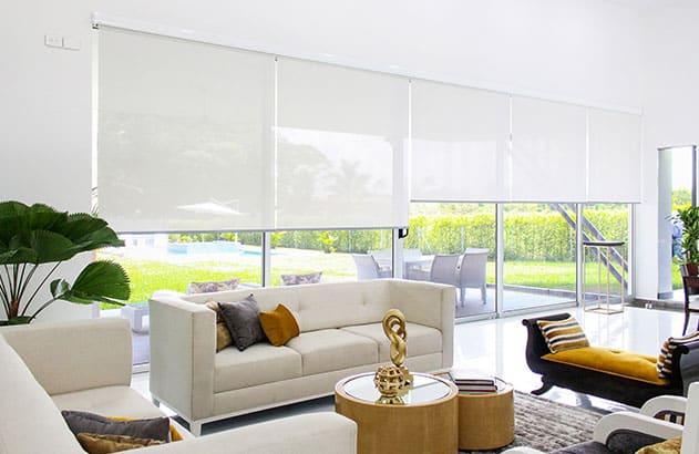Persianas y cortinas enrollables instaladas en una sala de gran ventanal