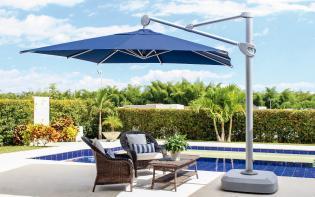 Sombrilla azul ubicada ala borde de una piscina
