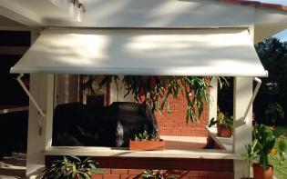 Toldo de brazo fijo instalado en el exterior de una casa de campo con vegetación