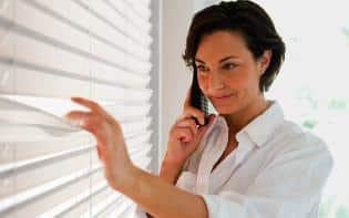 Mujer mirando por una ventana con una persiana Viewtex Pentagrama