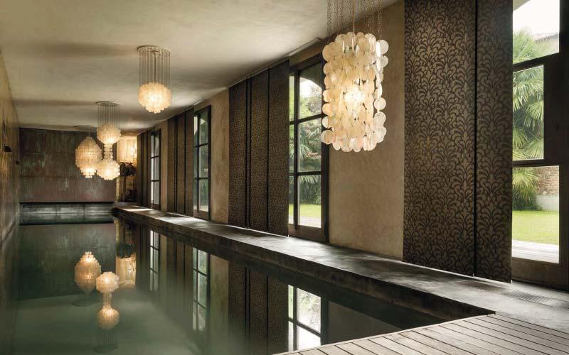 Piscina interior rodeada de ventanales con paneles Japoneses