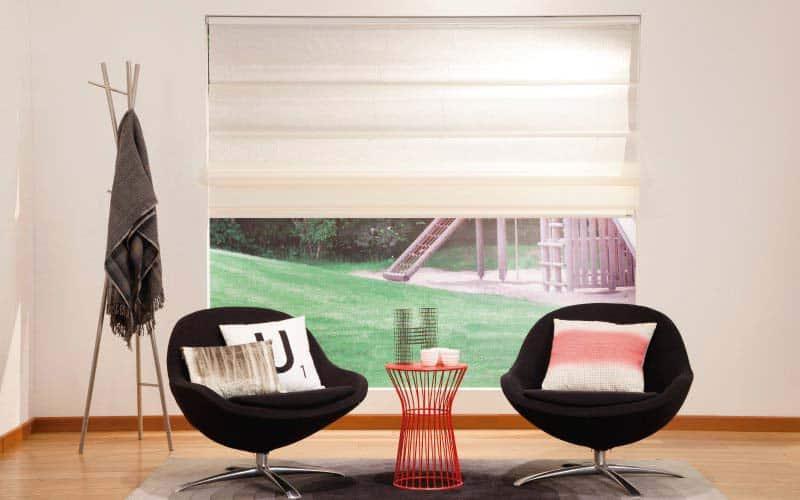 Sala pequeña con sillas negras y cortinas romanas en las ventanas