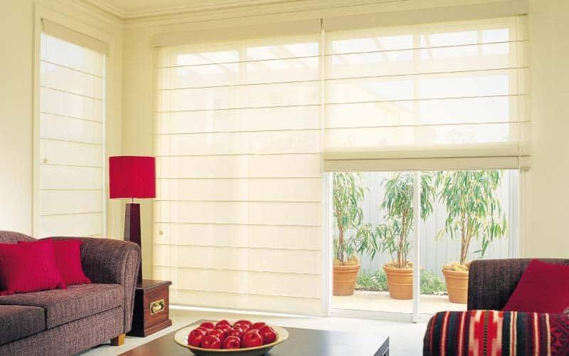 Sala moderna con cortinas romanas en las ventanas