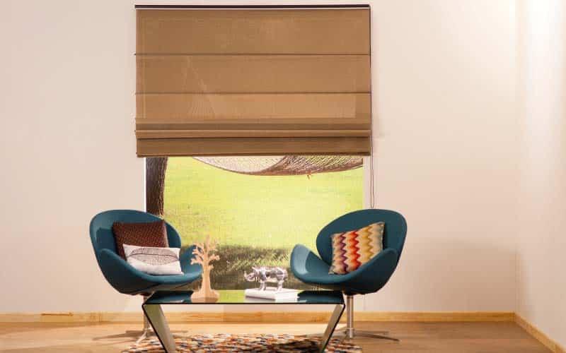 Sala con cortinas romanas y dos sillas verdes