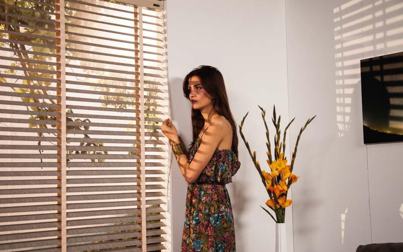 Mujer joven accionando manualmente unas persianas de madera Pentagrama