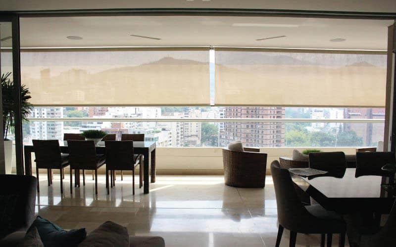 Toldo vertical Pentagrama instalado en un gran ventanal de una sala moderna
