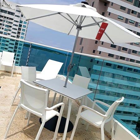 Sombrilla Alicante en una piscina con asolearas