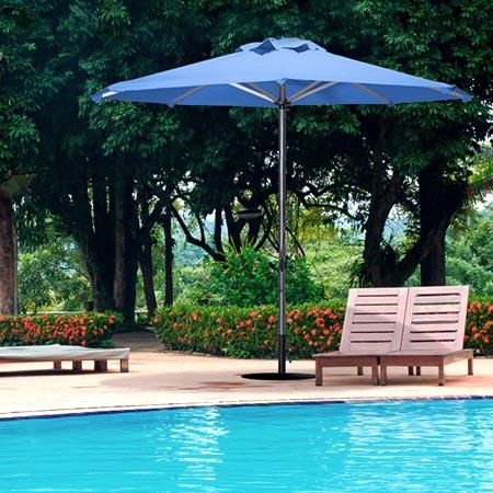 Sombrilla Limo redonda al lado de una piscina