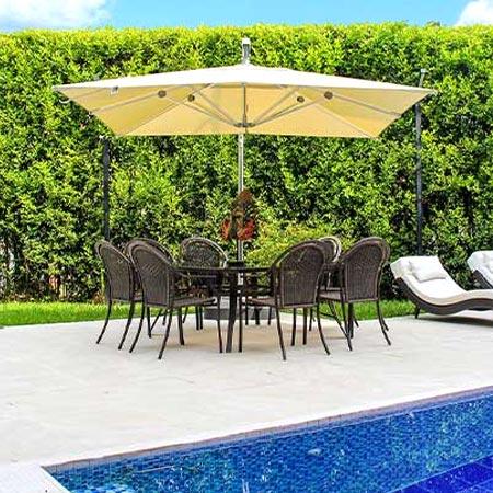 Sombrilla Menorca amarilla junto a una piscina