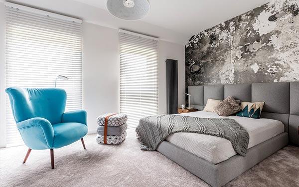 Persianas y cortinas Pentagrama decorando una habitación moderna con un a cama grande y una silla azul