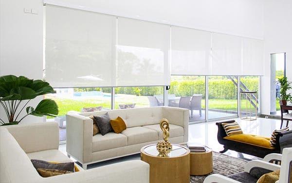 Cortinas y persianas enrollables en un gran ventanal de una sala moderna
