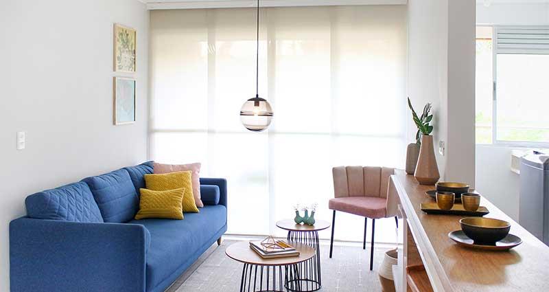 Persiana enrollable en una sala moderna con un sofa azul y lámpara de techo
