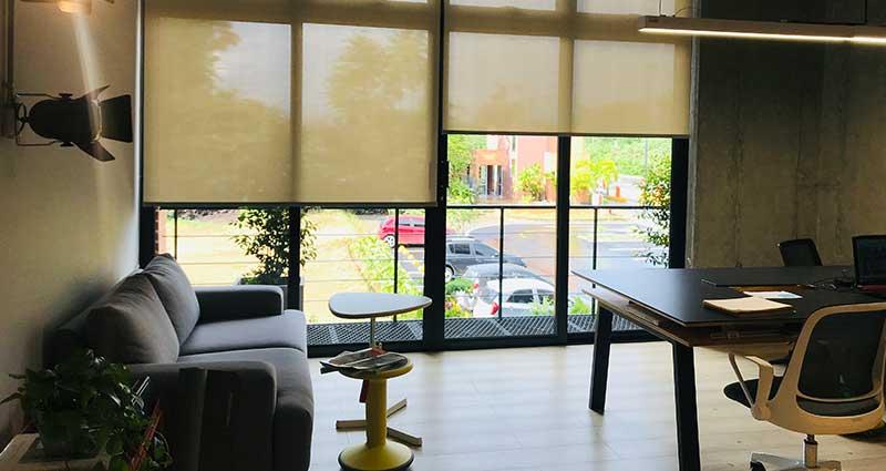 Sala moderna con un sofá oscuro y un ventanal con cortinas Enrollables traslúcidas