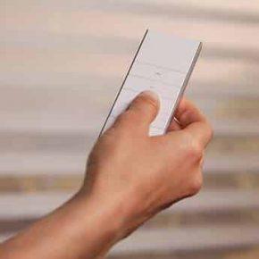 Persona accionando un control remoto Pentagrama para operar sus persianas y cortinas