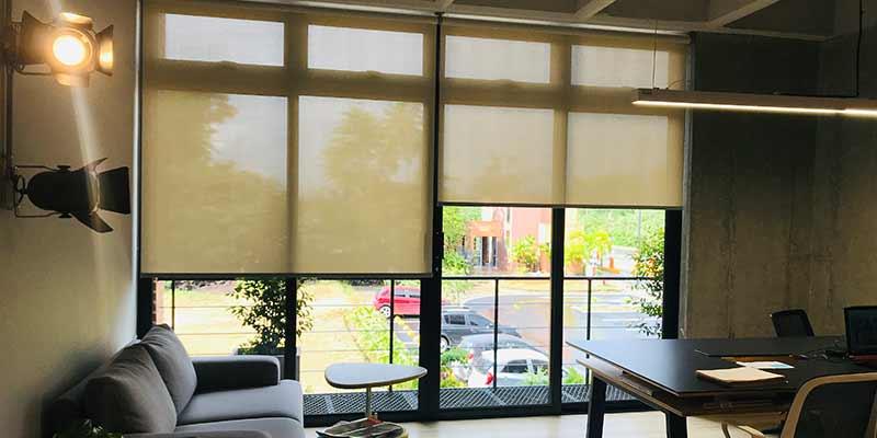 Persianas para oficinas pentagrama decorando una ventana de una oficina moderna con una sala