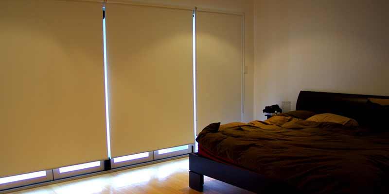 Habitación moderna con una cama oscura, y ventanales cubiertos por persianas enrollables con tejidos blackout