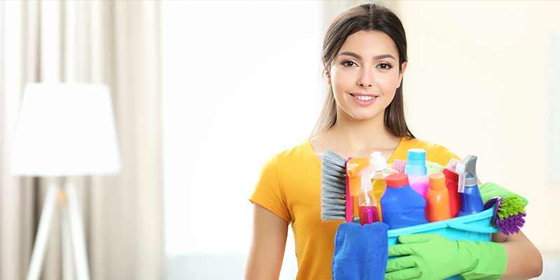 Mujer con productos de aseo para mantener su hogar limpio y saludable