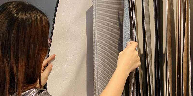 Persona observando materiales de cortinas y persianas en el nuevo centro de decoración Pentagrama